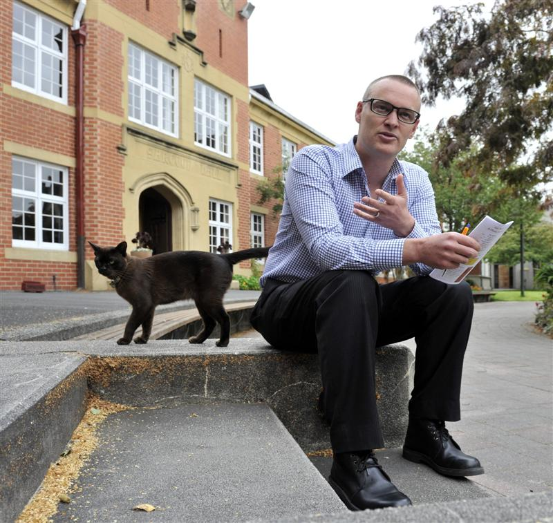Selwyn College warden Rev Dr David Clark takes some time out of preparing for the new wave of students, with college cat Ernie, in Dunedin. Photo by Gerard O'Brien